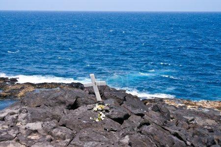 cruz por un muerto en una roca en el mar