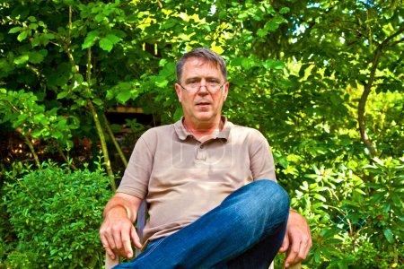 Friendly man sitting in his garden under a tree