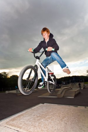 Joung red haired boy is jumping with his BMX Bike at the skate park