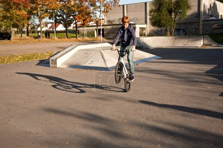 Boy with red hair is jumping with his BMX Bike at the skate park