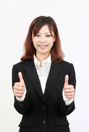 Smiling asian business woman showing thumbs up