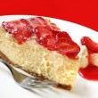 A slice of baked cheesecake topped with strawberry...