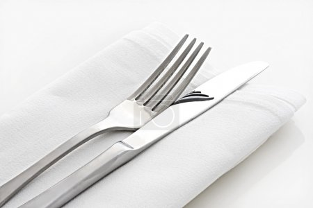 Photo for Silver knife and fork on white linen napkin. - Royalty Free Image