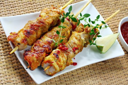 Photo for Chicken skewers served with chili, lime, thyme, and a chili dipping sauce. - Royalty Free Image