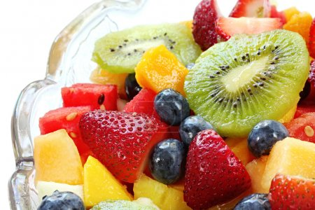 Photo for Fresh fruit salad in a crystal bowl. Luscious healthy eating, with kiwi fruit, strawberries, blueberries, canteloupe, watermelon, mango, oranges, and passionfr - Royalty Free Image
