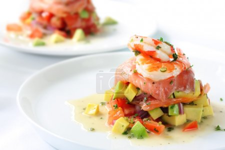 Photo for Smoked salmon with an avocado and tomato salsa, topped with king prawns. - Royalty Free Image