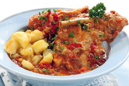 Photo pour Jarret d'agneau, mijotés avec des tomates, de poivron et d'oignons, servi avec pommes de terre rôties « brisés ». yum! - image libre de droit