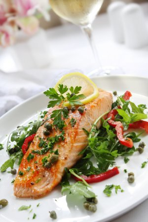 Photo for Grilled Atlantic salmon with a rocket salad, capers, parsley and lemon. - Royalty Free Image