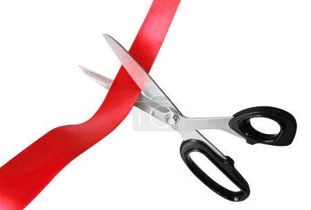 Photo pour Ciseaux coupant à travers le ruban ou ruban rouge, isolés sur blanc . - image libre de droit
