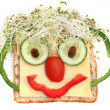 Face on bread, made from cheese, sprouts, capsicum...