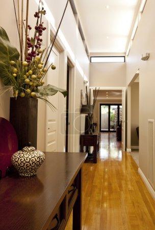 Photo pour Hall d'entrée de la maison, avec des lames de plancher polis, éclairage vers le bas et une décoration élégante nouvelle vitrine. - image libre de droit