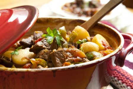Photo for Traditional goulash or beef stew, in red crock pot, ready to serve. Shallow DOF. - Royalty Free Image