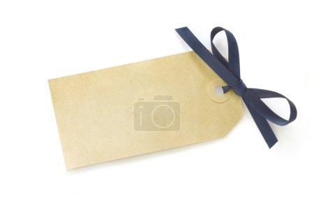 Photo pour Étiquette-cadeau vide à égalité avec noeud de ruban de satin bleu. ombre doux sur la surface blanche. - image libre de droit