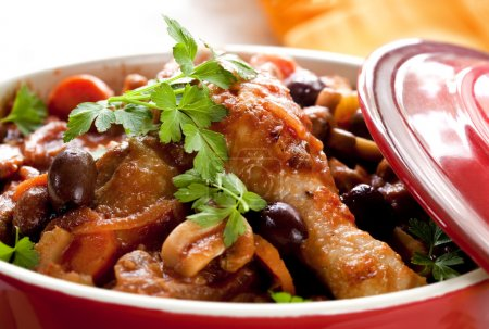 Photo for Chicken cacciatore in a red crock pot, ready to serve. Shallow DOF. - Royalty Free Image