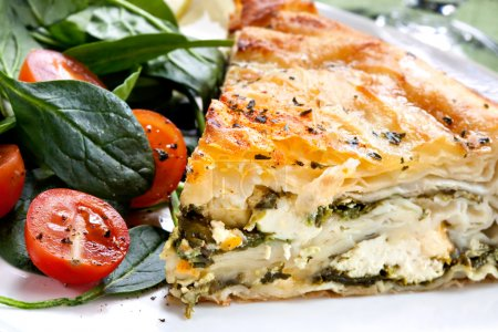 Photo for Delicious spinach and feta cheese pie, with filo pastry. Traditional Greek spanakopita, with salad. - Royalty Free Image