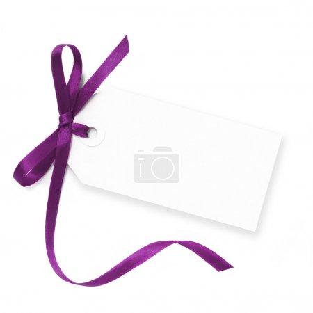 Photo pour Étiquette-cadeau vide à égalité avec un noeud de ruban de satin violet. isolé sur blanc avec ombre doux. - image libre de droit