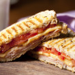 Grilled sandwich with ham, cheese and tomato, and ...