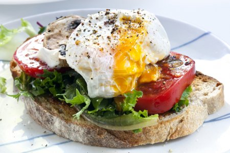 Photo for Poached egg on sourdough toast, with grilled tomatoes, mushrooms and salad leaves. A healthy, delicious breakfast or brunch. - Royalty Free Image