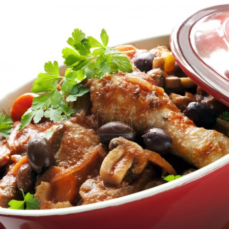 Photo for Traditional chicken cacciatore, in a red casserole dish. - Royalty Free Image