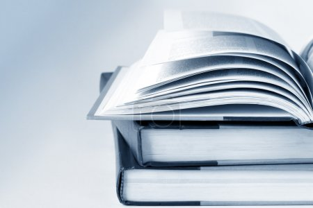 Photo for Open Book on top of closed books. Blue toned image, shallow depth of field. - Royalty Free Image