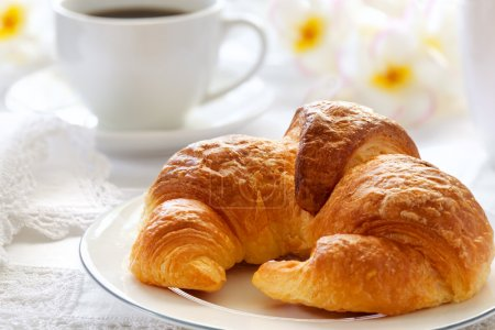 Photo for Croissant with coffee, on sunlit breakfast table with lace napkins. - Royalty Free Image
