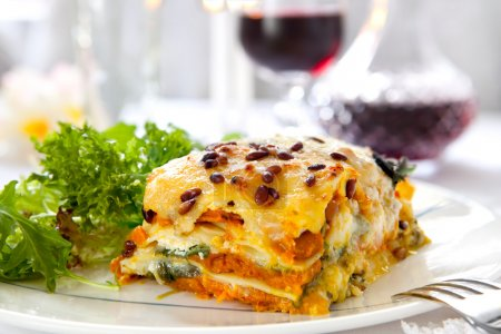 Photo for Vegetarian lasagne topped with toasted pine nuts and melting cheeses. With salad and red wine. - Royalty Free Image