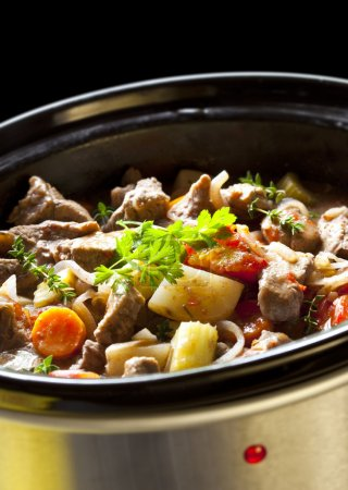 Photo for Beef stew cooking in a clow cooker. Hearty warming winter food. - Royalty Free Image