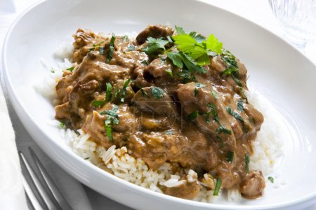 Photo for Beef stroganoff over white rice, garnished with parsley. - Royalty Free Image