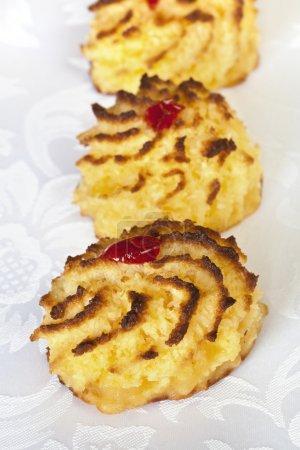 Photo pour Macarons à la noix de coco garnis de cerises glacées. Focus sur le macaron avant . - image libre de droit