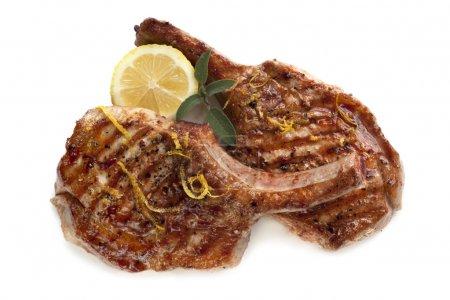 Photo pour Escalopes de porc grillé, isolés sur blanc, garni de citron et sauge. - image libre de droit