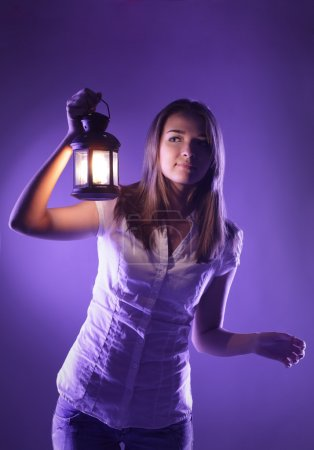 Photo for Beautiful girl with lantern seeking in night - Royalty Free Image