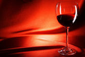 Red wine glass on a red background