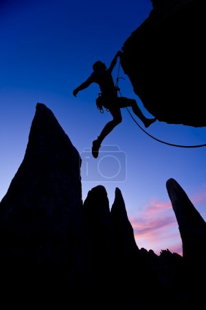 Rock climber dangling by one arm.