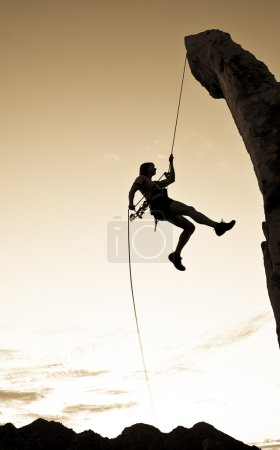 Rock climber rappelling.