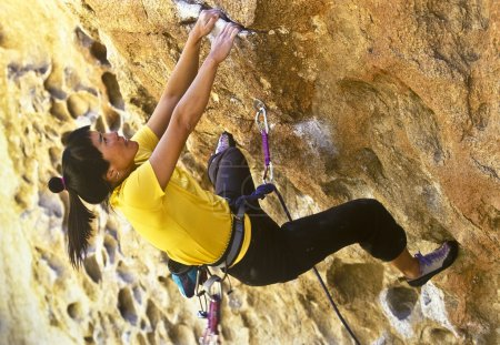 Photo for Female climber clinging to the grips of a steep rock wall. - Royalty Free Image