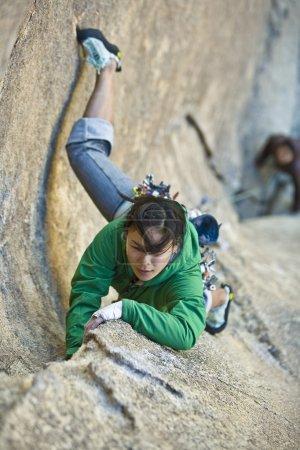 Photo pour Climber se concentre sur son prochain mouvement dans le parc national Joshua Tree, en Californie, sur une formation rocheuse fraîche et ombragée . - image libre de droit