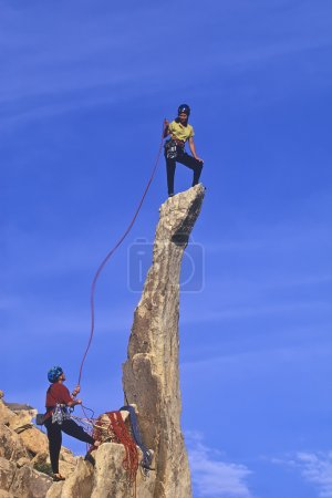 Photo for Team of rock climbers struggle up a challenging cliff. - Royalty Free Image