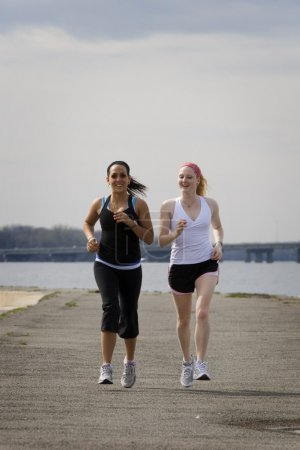 Two women jogging on cloudy day