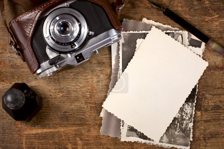 Vintage ink and pen, old photos and camera on old wooden table