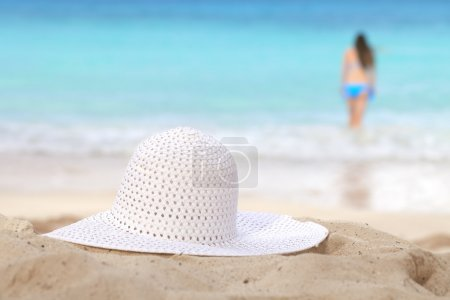 White sun hat on beach girl going to swim and sea on background