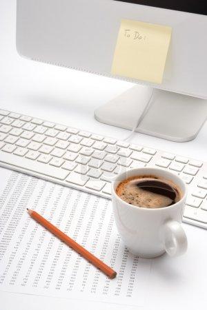 Photo pour Lieu de travail de bureau avec café, crayon, feuille avec numéros, clavier et blanc À faire liste sur ordinateur - image libre de droit