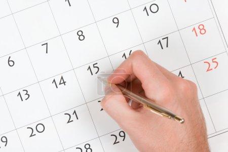 Photo pour Main avec stylo prendre une note dans le calendrier - image libre de droit
