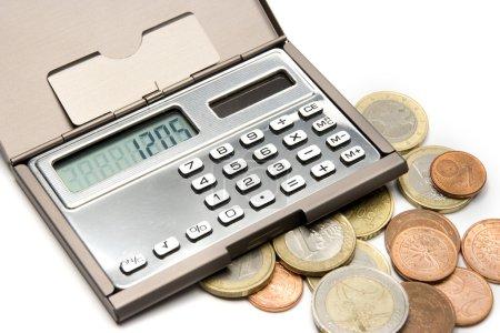 Photo pour Argent calcul concept - pièces de monnaie et les calculatrice sur fond blanc - image libre de droit