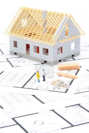 Photo pour Construire le concept de la maison - modèle de la maison avec des matériaux de construction, des figures du constructeur et des plans - image libre de droit