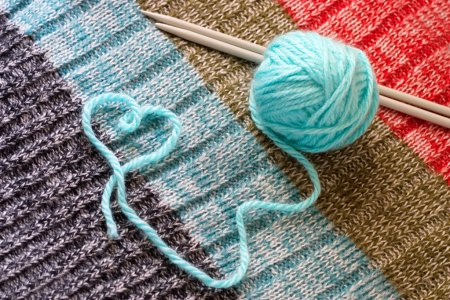 Blue wool and knitting needles, thread in form of ...