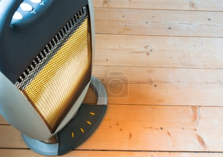 A halogen or electric heater on wooden floor
