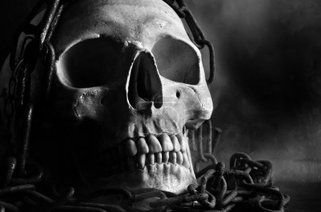 Human skull with chain and smoke in black and white