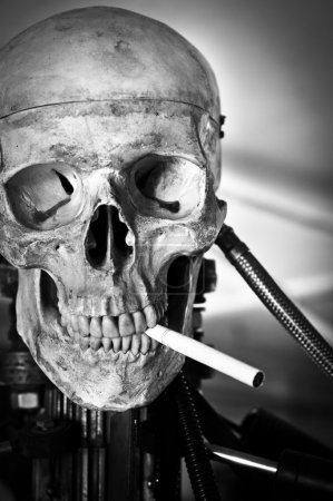 Closeup of a human skull on robot body with cigarette in mouth