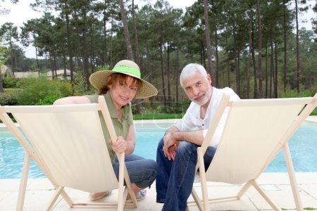 Photo pour Couple de personnes âgées assis dans des chaises longues, une piscine - image libre de droit
