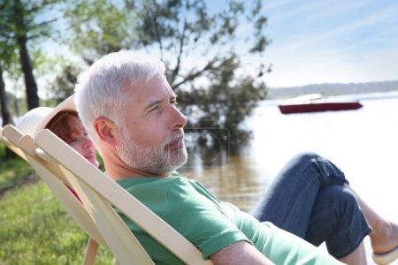 Photo pour Couple de personnes âgées au repos en chaise longue - image libre de droit